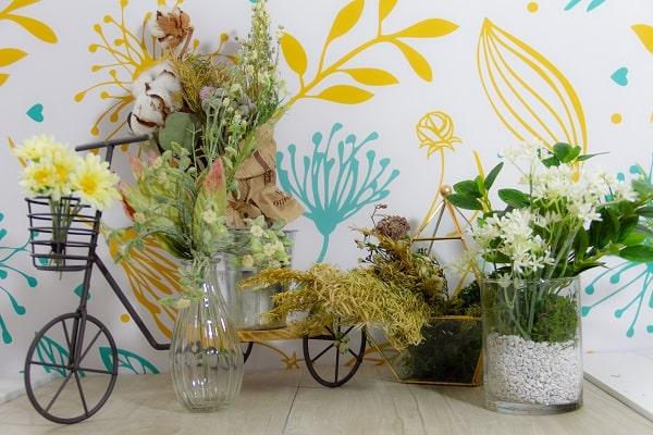 ボタニカルなスクリーンとドライフラワーや花瓶が飾られたフォトブース